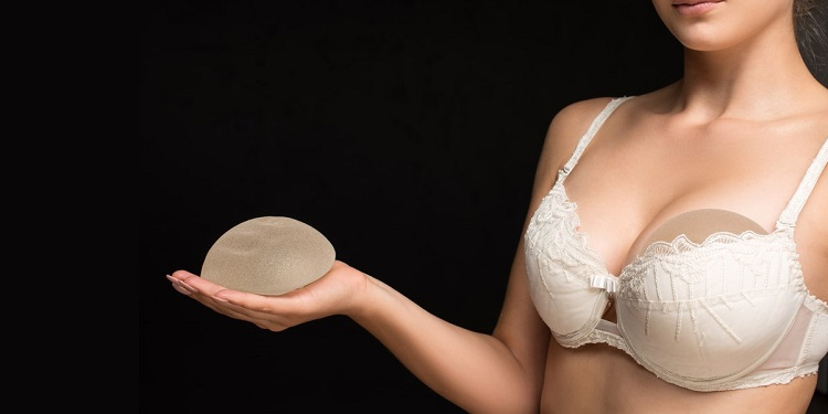 Woman holding breast implant